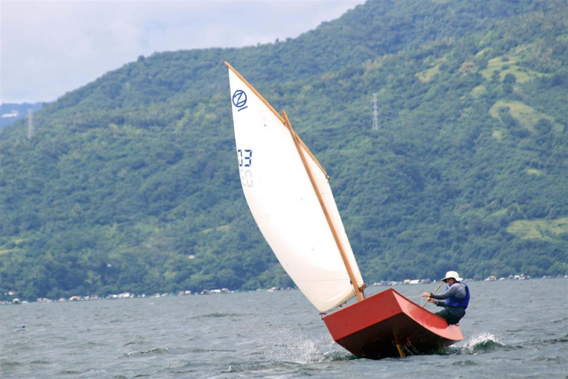 Oz Goose club racing dinghy jumping over a wave